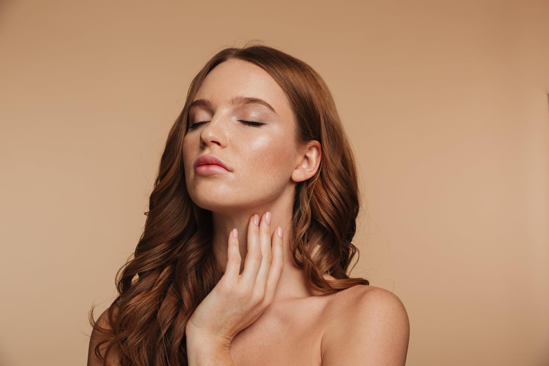 Mujer aplicando productos con vitamina E para prevenir el envejecimiento de la piel